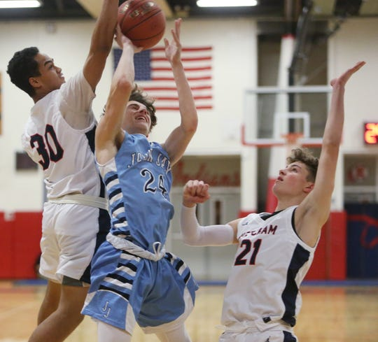John Jay's John Bartusiak goes up for a shot and is contested by Ketcham's Phoenix Bowman (30) and Owen Paino (21) during a boys basketball game Thursday.