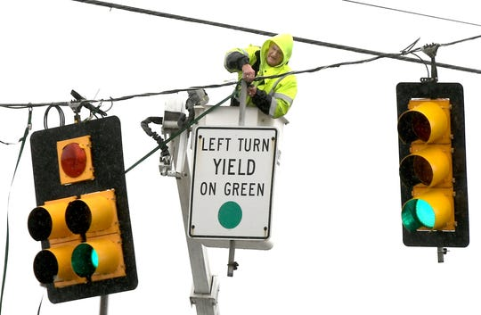 """Milt Sultzbaugh, 78, owner of Milt's Repair Service in Windsor, braves high winds to repair a traffic light at Lombard and Cape Horn roads after severe weather moved through the county during the morning Friday, Feb. 7, 2020. He said winds ripped the tethers on the lights and signage. Asked why he didn't send a younger crew member to do the repair, he said, """"They've got longer to live than me."""" Bill Kalina photo"""