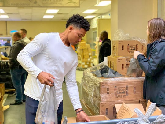 Baltimore Orioles shortstop Richie Martin, left, sorts frozen apricots while volunteering at the York County Food Bank. The stop in York marked the start of the Orioles' Birdland Caravan community service tour.