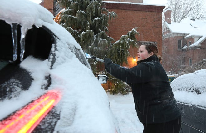 Ashley Potter, Rochester, scrapes ice off her car before heading to work as winter moved back into western New York with first ice, then snow, Friday, Feb. 7, 2020 in Rochester.