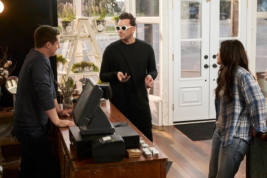 Characters Patrick Brewer, David Rose and Stevie Budd stand inside the Rose Apothecary store in this screen capture from an episode of Schitt's Creek.