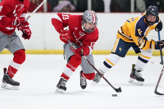 Lucas Schwartz (13) of Canandaigua moves the puck through center ice during a high school hockey game against Victor.