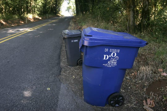 A blue recycling bin from D&O Garbage and Recycling, sits waiting for pickup along Skyline S. in Salem.