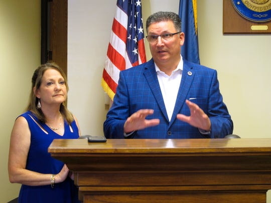 In this Aug. 7, 2019 file photo, Treasurer John Schroder speaks after qualifying for his re-election bid, joined by his wife Ellie in Baton Rouge, La.   Gov. John Bel Edwards is suing Louisiana's state treasurer for blocking a $25 million fund transfer the governor and lawmakers earmarked for state operating expenses.