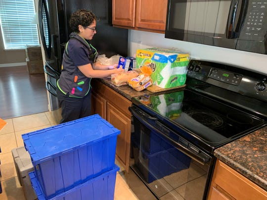 "Vero Beach's Walmart InHome Delivery associate Amanda Swanson places items that don't need to be refrigerated on the kitchen counter of the store's ""test home."" Associates selected for InHome Delivery are background checked and must activate a body camera, worn at all times, before entering the customer's home."