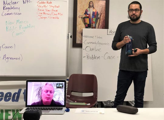 Tyson Slocum, energy program director for Washington, D.C.-based Public Citizen, on laptop screen, talks via a livestream about the pending El Paso Electric sale to people at a Sunrise El Paso environmental group community meeting  Jan. 31. Dominic Chacon, a Sunrise El Paso organizer, listens.