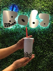 """Bigstraw Boba owner Richard Tran serves as the hand model for a taro ice smoothie with boba. """"We buy it, we peel it and we cook it,"""" Tran says of the taro root, which gives the drink its purple hue."""