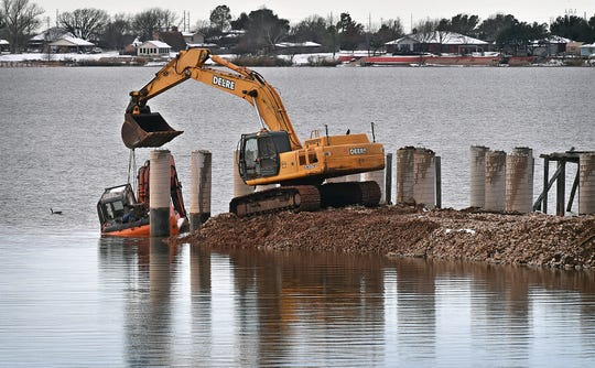 Construction workers attach cables to a small excavator which ended up in the water Friday morning during work on the Lake Wichita boardwalk. They attempted to use the larger machine to retrieve the smaller one.