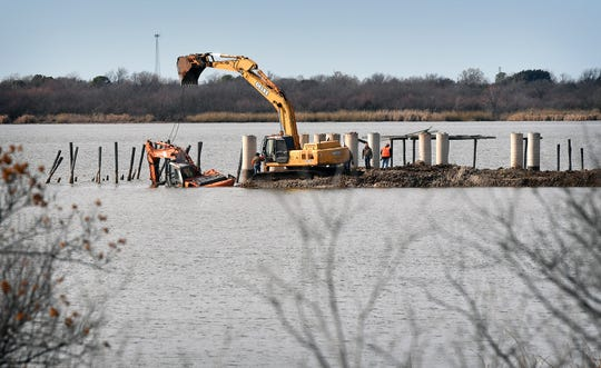 Workers for Trinity Hughes Construction attempt to retrieve a small excavator with a larger excavator after the first wound up in the water during construction of the Lake Wichita boardwalk Friday morning.