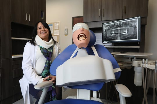 Misti Malfe, program director for Hocking College's Dental Hygiene Program, and George, a dental hygiene mannequin, are shown in the New Lexington clinic.