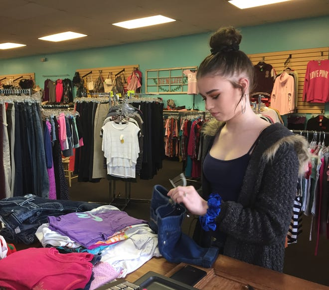 Michaela, 14, tags clothing for sale at New Life Thrift Store. Even after completing her 120-hour community service credit for school, Michaela continues to work at the thrift store.