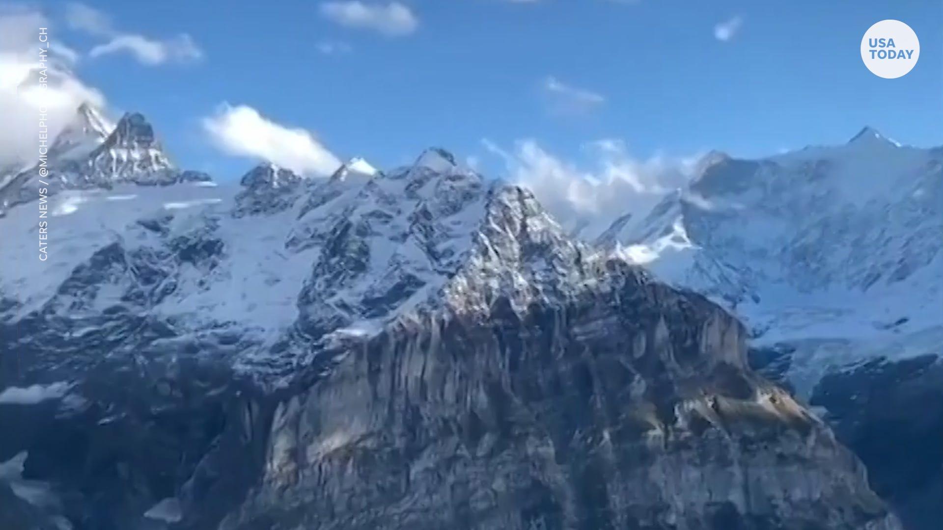 Woman standing on platform captures beautiful view of Swiss Alps