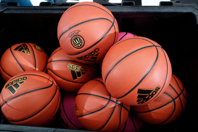 A general view of basketballs in a bin.