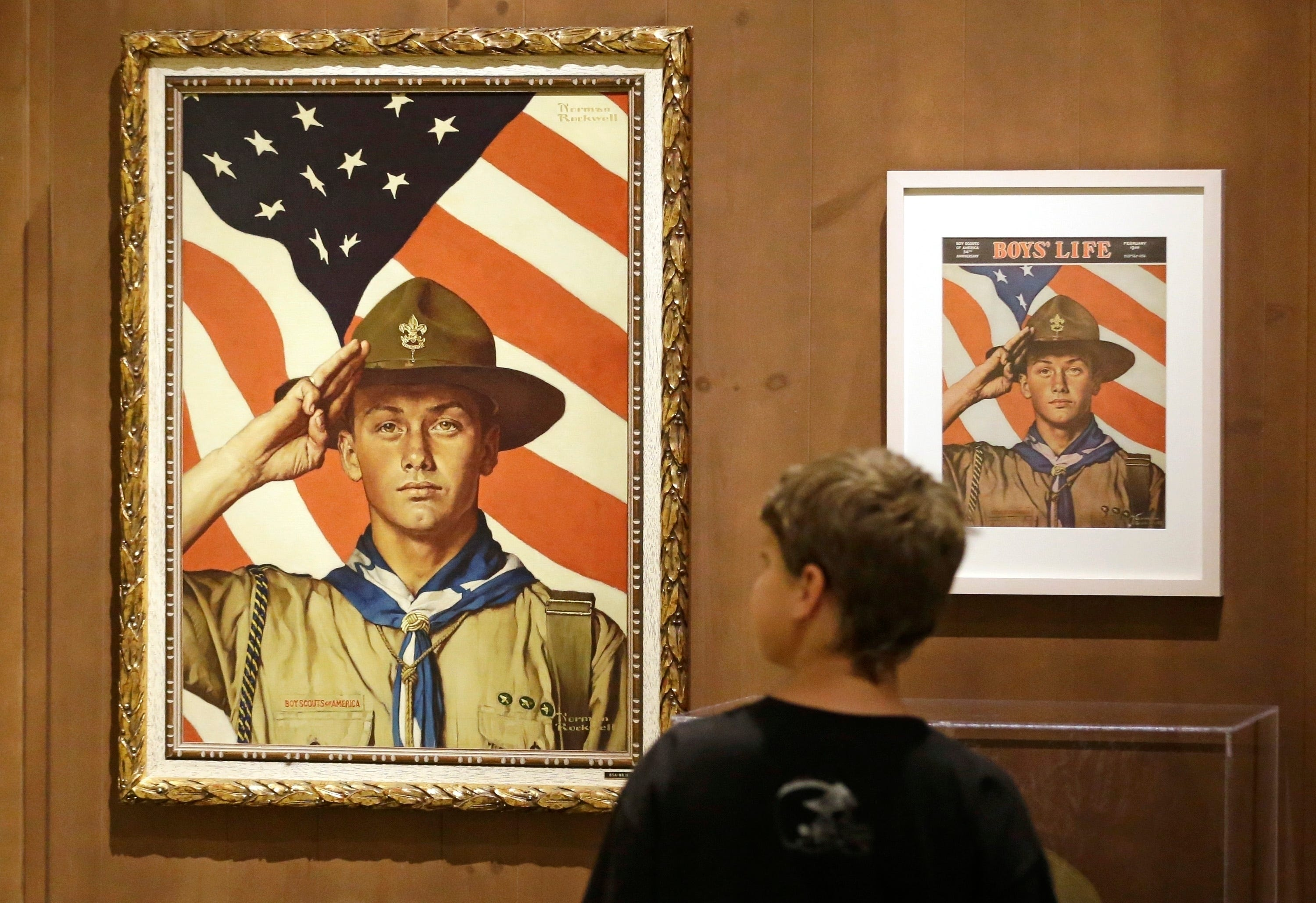 A child looks over a Norman Rockwell exhibit in Salt Lake City. Rockwell started his career creating illustrations for the Boy Scouts' Hike Book. The Scouts still own about 70 of the famed artist's works.