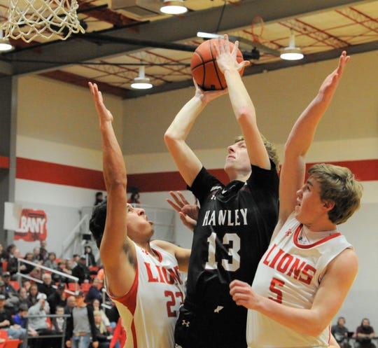 Hawley senior Jaron Reynolds (13) goes for a shot as Albany's Ben West (23) and Cade Neve (5) defend on Friday, Feb. 7, 2020, at Albany High School.