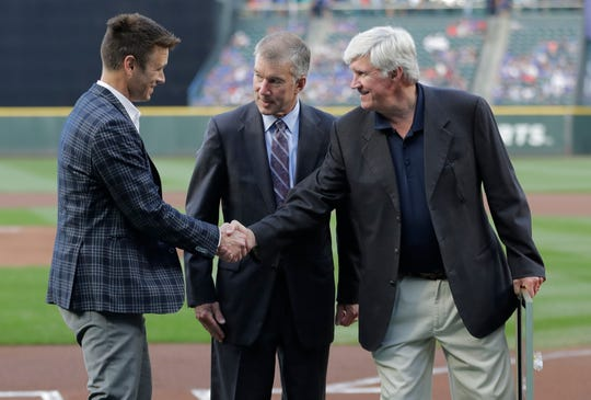 In this Aug. 3, 2018 file photo, Seattle Mariners general manager Jerry Dipoto, left, President Kevin Mather, center, and owner John Stanton, right, take part in a ceremony before a baseball game against the Toronto Blue Jays in Seattle. Spring training for the Mariners ahead of the 2020 season will feature young players and prospects that could be at the heart of whether the Mariners' rebuild plans ultimately work.
