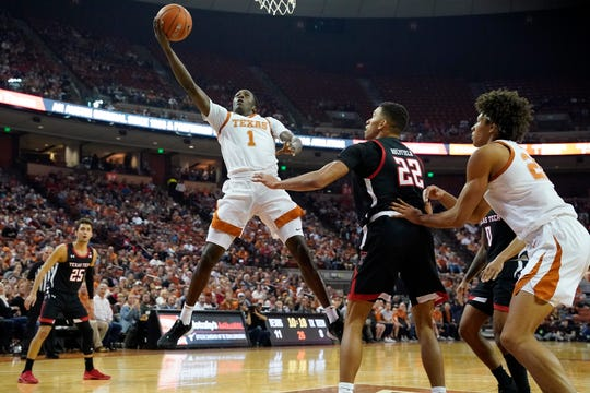 Feb 8, 2020; Austin, Texas, USA; Texas Longhorns guard Andrew Jones (1) shoots over Texas Tech Red Raiders forward TJ Holyfield (22) in the first half at Frank C. Erwin Jr. Center. Mandatory Credit: Scott Wachter-USA TODAY Sports