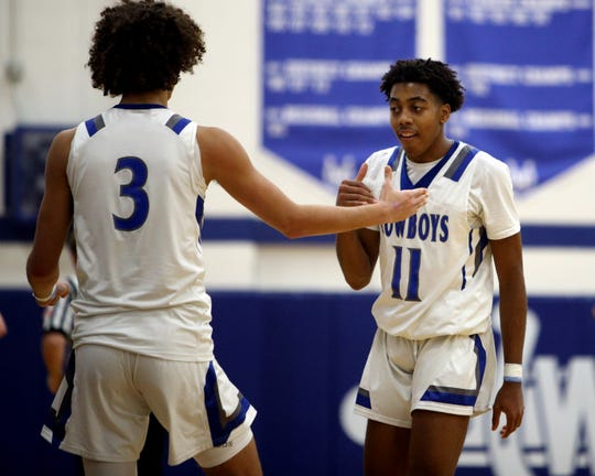 Wyoming junior Isaiah Walker [11] is congratulated by teammate Evan Prater after scoring his 1,000th point for the Cowboys in their 71-56 win over Taylor Feb. 7.
