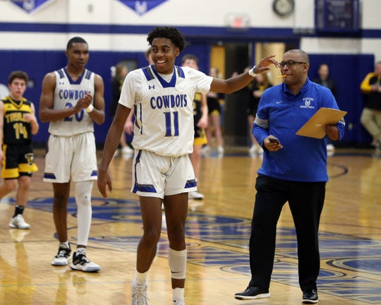 Wyoming junior Isaiah Walker [11] is congratulated by varsity assistant and JV coach Mike Pearl after scoring his 1,000th point for the Cowboys.