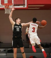 Lakota East center Alex Mangold (11) tries to block a shot by Princeton guard Deairius Randle (3) during their basketball game Friday, Feb. 7, 2020.