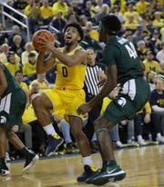 Michigan guard David DeJulius scores against Michigan State forward Gabe Brown during the first half Saturday, Feb. 8, 2020 at the Crisler Center in Ann Arbor.