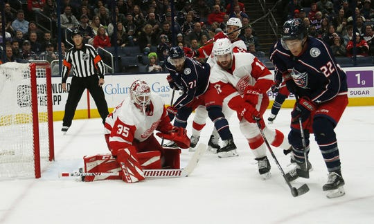 Columbus Blue Jackets' Sonny Milano and Detroit Red Wings' Filip Hronek battle for the puck in front of goalie Jimmy Howard during the first period in Columbus, Ohio, on Friday, Feb. 7, 2020.