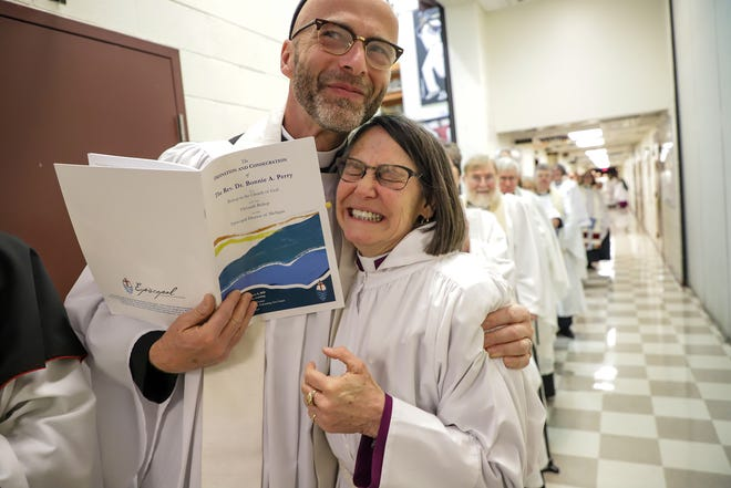 Dr. Bonnie Perry receives a hug from Rev. Dan Scheid, of St. Paul's Episcopal Church in Flint, before the ceremony where she  will be ordained as the 11th Episcopal Bishop of the Episcopal Diocese of Michigan on February 8, 2020 at the Ford Community & Performing Arts Center in Dearborn, Mich. Perry will become the first woman bishop as well as the first lesbian bishop in the diocese since it was formed in 1836.