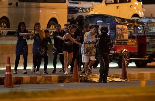 People who were able to get out of Terminal 21 Korat mall are escorted outside by armed commando soldiers in Nakhon Ratchasima, Thailand on Sunday, Feb. 9, 2020.