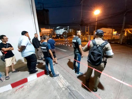 Police and bystanders stand near the scene of a shooting at the Terminal 21 mall, in Korat, Thailand, Saturday, Feb. 8, 2020.