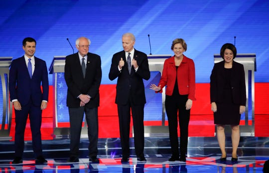 From left, Democratic presidential candidates former South Bend Mayor Pete Buttigieg, Sen. Bernie Sanders, I-Vt., former Vice President Joe Biden, Sen. Elizabeth Warren, D-Mass., and Sen. Amy Klobuchar, D-Minn., stand on stage Friday, Feb. 7, 2020, before the start of a Democratic presidential primary debate hosted by ABC News, Apple News, and WMUR-TV at Saint Anselm College in Manchester, N.H.