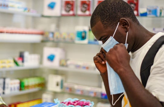 A man tries on a face mask Feb. 6. at a pharmacy in Kitwe, Zambia.