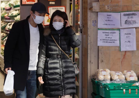 """People wear masks as they shop in China Town in London, Friday, Feb. 7, 2020. The director-general of the World Health Organization says a drop in the number of new coronavirus cases for two days is """"good news"""" but cautions against reading too much into that. China reported 31,161 cases in mainland China in its update Friday."""