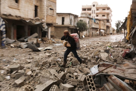 A man carries his belongings through a street destroyed in recent bombings by the Syrian government forces in the town of Sarmin, in Idblib province, Syria, Friday, Feb. 7, 2020.