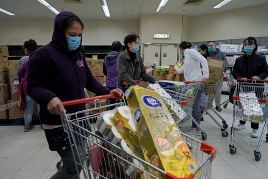 Customers wearing masks, purchase tissue papers in a supermarket in Hong Kong, Saturday, Feb. 8, 2020.