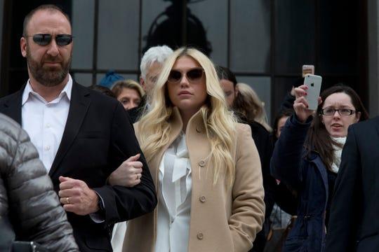 Pop star Kesha, center, leaves Supreme court in New York, Friday, Feb. 19, 2016.