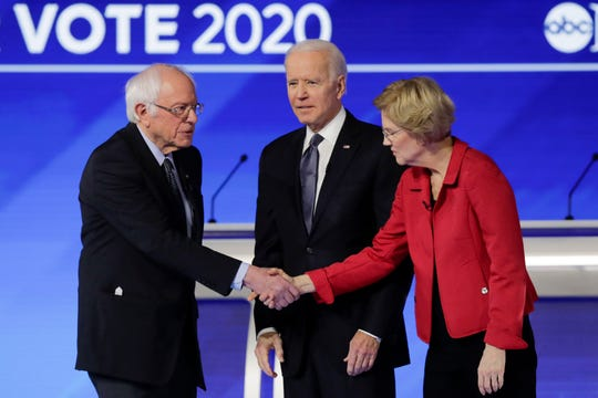 From left, Democratic presidential candidate Sen. Bernie Sanders, I-Vt., shakes hands with Sen. Elizabeth Warren, D-Mass., as former Vice President Joe Biden watches on stage Friday, Feb. 7, 2020, before the start of a Democratic presidential primary debate hosted by ABC News, Apple News, and WMUR-TV at Saint Anselm College in Manchester, N.H. (AP Photo/Charles Krupa)