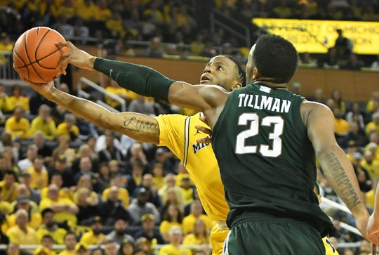 Michigan State forward Xavier Tillman (23) gets his hand on the ball being shot by Michigan guard Zavier Simpson (3) in the second half.