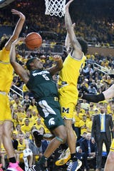 Michigan State guard Cassius Winston (5) tries to shoot between Michigan forward Brandon Johns Jr., left, and Michigan guard Eli Brooks, right, in the first half.