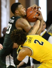 Michigan forward Isaiah Livers (2) and Michigan State forward Xavier Tillman (23) battle for a rebound in the second half.