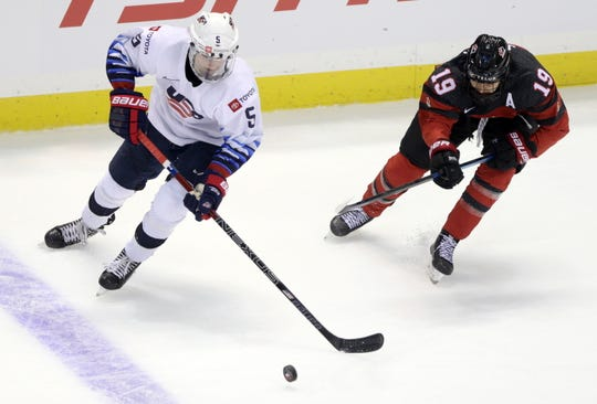 Farmington's Megan Keller, left, is checked by Team Canada's Brianne Jenner during a game in the Rivalry Series in Victoria.