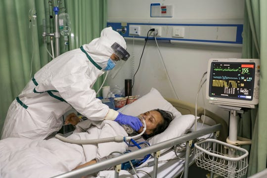A nurse gives water to a patient in the isolation ward for 2019-nCoV patients at a hospital in Wuhan in central China's Hubei province.
