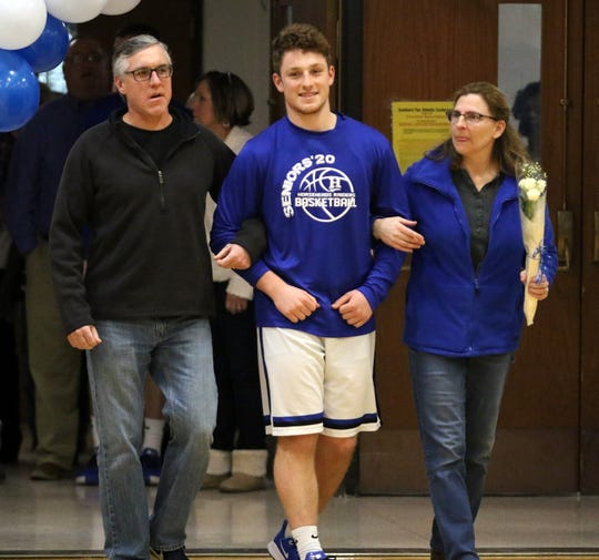 Henry Juan is accompanied by his parents, Bill and Mary Juan, during Senior Night against Binghamton on Feb. 8, 2020 at Horseheads Middle School.