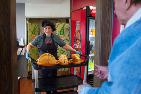 Los Alfaro's Latin Restaurant owner Teresa Alfaro leaves the kitchen with four Footlong Tacos for tournament participants Saturday afternoon, Feb. 8, 2020.
