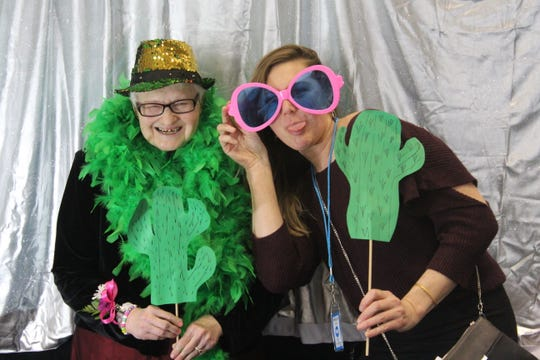 "Edna Nickols, wearing a green feather boa, and Shelley Rogers pose at a photo station Friday at the annual  ""Night to Shine"" prom at Terra State Community College."