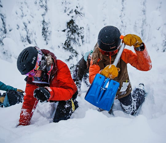 Madison Browning, left, and Sarah Schmidt practice their digging speed and technique during a ladies level one avalanche course at Whitefish Mountain Resort on Jan. 31, 2020. (Hunter D'Antuono/Flathead Beacon via AP)