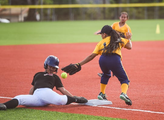 Simon Sanchez High's Reanna Blas slides to third base during an Interscholastic Sports Association Softball game against the Guam High Panthers at Guam High School Field in this Feb. 8 file photo. A schedule change will allow Guam High to compete in the playoffs after it announced it would pull out of sports activities over coronavirus concerns.