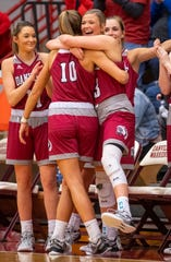 Danville High School senior Ella Collier (13), right, celebrates the team's victory with senior Katie Davis (10) as time expires in an IHSAA Girls' Basketball Sectional semifinal game, Friday, Feb. 7, 2020, at Danville High School. Danville won 54-41 to advance to Saturday night's sectional championship game.