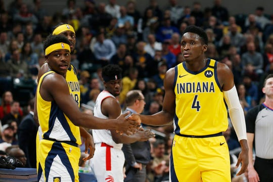 Feb 7, 2020; Indianapolis, Indiana, USA; Indiana Pacers guard Victor Oladipo (4) high fives guard Aaron Holiday (3) as he walks to the bench in a game against the Toronto Raptors during the first quarter at Bankers Life Fieldhouse. Mandatory Credit: Brian Spurlock-USA TODAY Sports