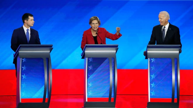 Democratic presidential candidate Sen. Elizabeth Warren, D-Mass., speaks as former South Bend Mayor Pete Buttigieg, left, and former Vice President Joe Biden listen during a Democratic presidential primary debate on Friday, Feb. 7, 2020, hosted by ABC News, Apple News and WMUR-TV at Saint Anselm College in Manchester, N.H.