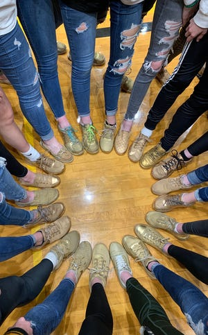 Benton Central girls basketball players painted their shoes gold prior to Friday's sectional semifinal against Peru to honor Dick Atha.